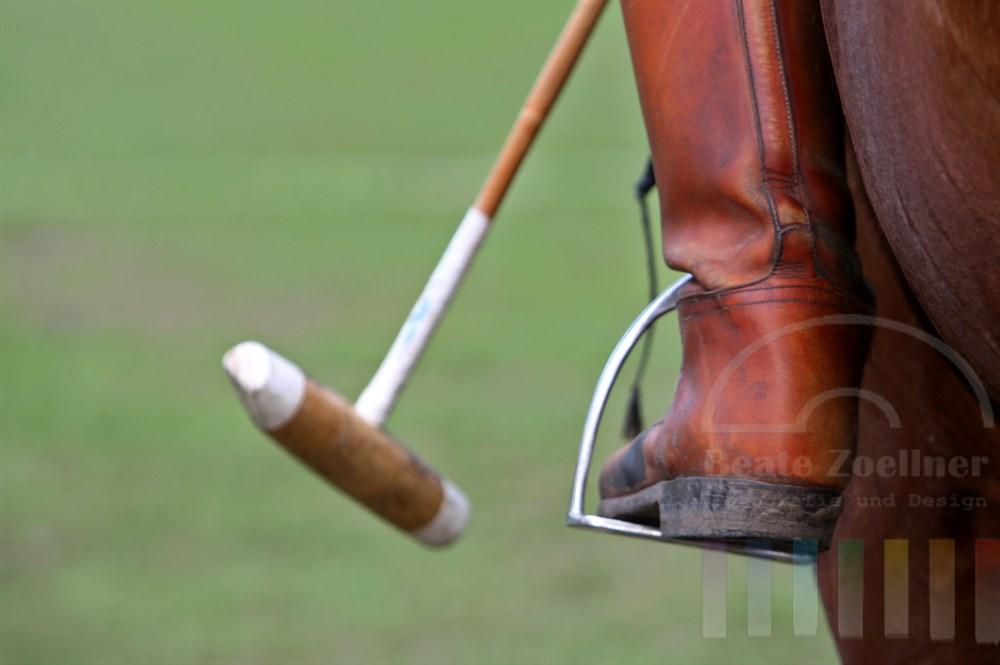 Symbolbild für den Polosport: Reitstiefel im Steigbügel am Pferdeleib, im Hintergrund der Poloschläger und grüner Rasen