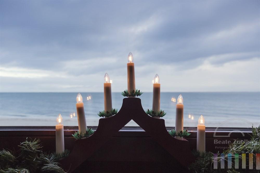 Weihnachtlicher Lichterbogen am Fenster mit Ausblick auf das Wattenmeer vor Hörnum/Sylt