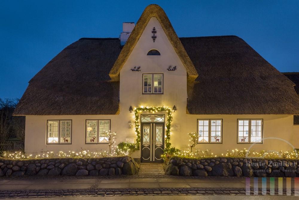 Weihnachtlich geschmücktes und beleuchtetes Friesenhaus mit Reetdach in Keitum/Sylt zur blauen Stunde