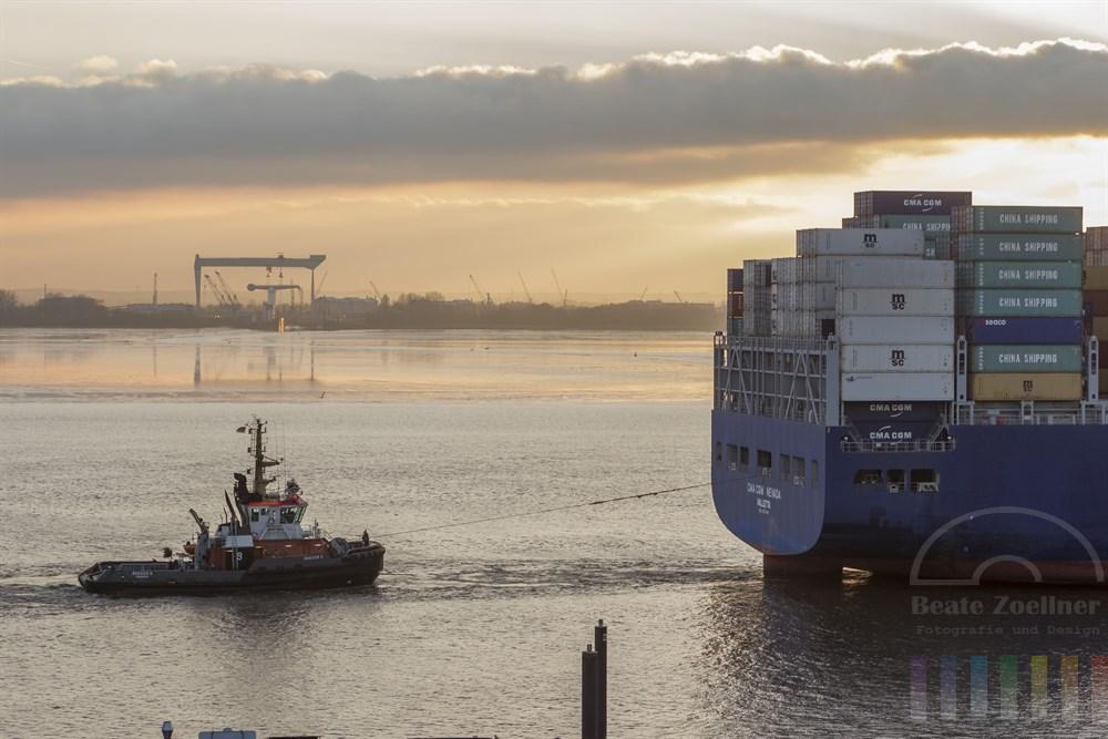Blick vom Blankeneser Treppenviertel auf die Elbe: Ein Bugsier-Schlepper stabilisiert die Fahrt eines Containerschiffes Richtung Elbmündung, Abendstimmung. Am anderen Elbufer die Sietas-Werft.