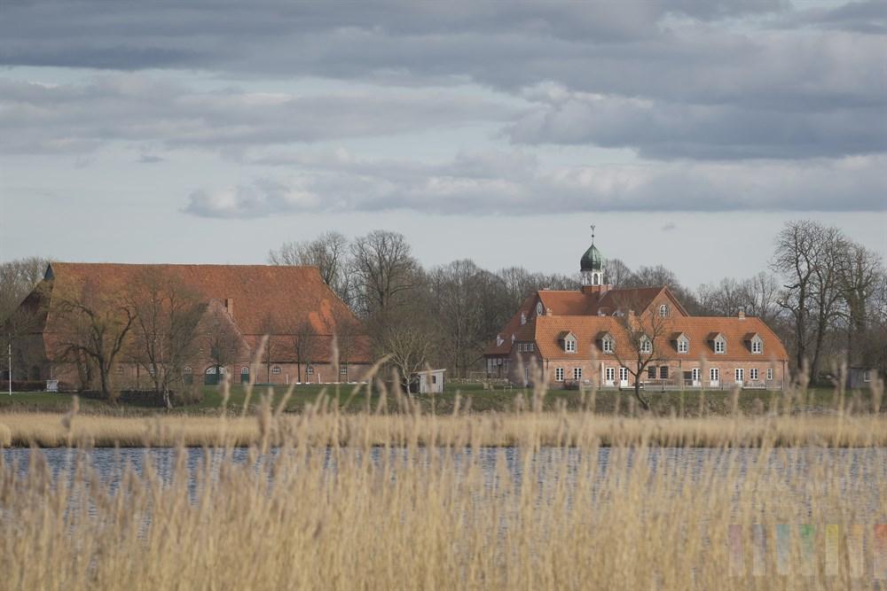 Blick über die Schlei bei Lindaunis auf das historische Gut Stubbe, das heute noch als landwirtschaftlicher Betrieb geführt wird