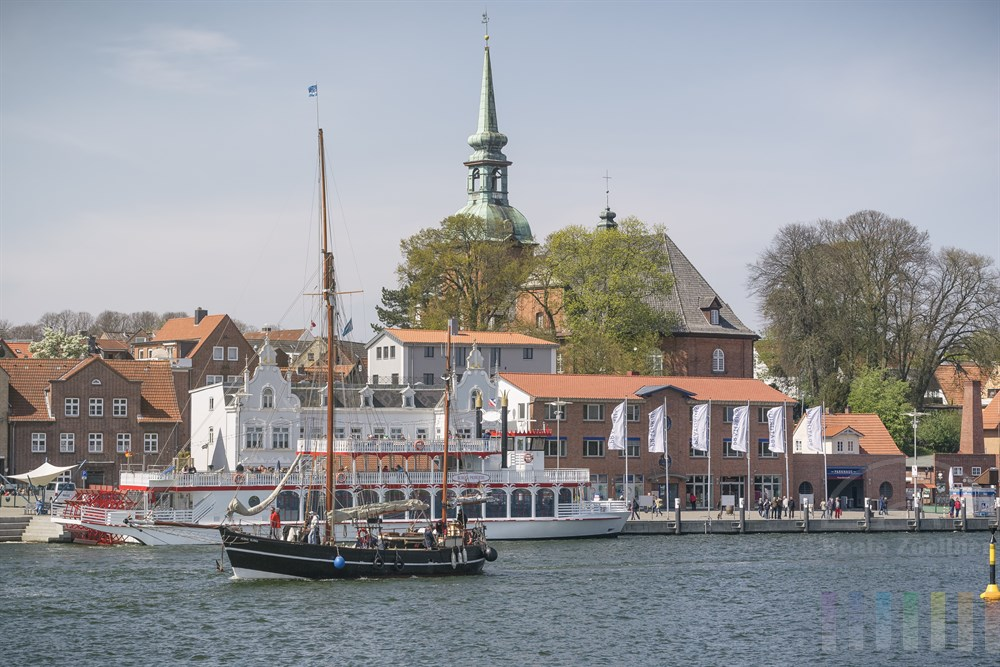 Blick von der Klappbrücke über die Schlei auf das frühlingshafte Kappeln mit der St. Nikolai Kirche, sonnig, frühlingshaft. Zahlreiche Schiffe und Boote passieren die jetzt freie Durchfahrt