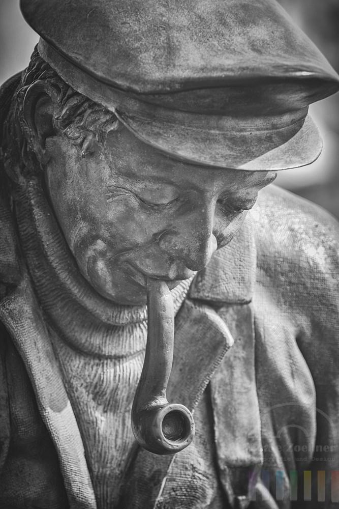 """Detail der Bronze-Figur """"Peter-Aal"""", schwarzweiß. Die Statue wurde vom Bildhauer Bernd Maro geschaffen und steht seit 1999 am Sportboothafen in Maasholm an der Schlei. Das Denkmal des Fischers erinnert daran, dass früher in harten Wintern das """"Aalstechen"""" oft die einzige Möglichkeit war, den Lebensunterhalt für die Familien zu verdienen. Seit 1960 ist diese uralte Methode, bei der die Aale (in Winterruhe) durch ein Eisloch aufgespießt werden, verboten"""