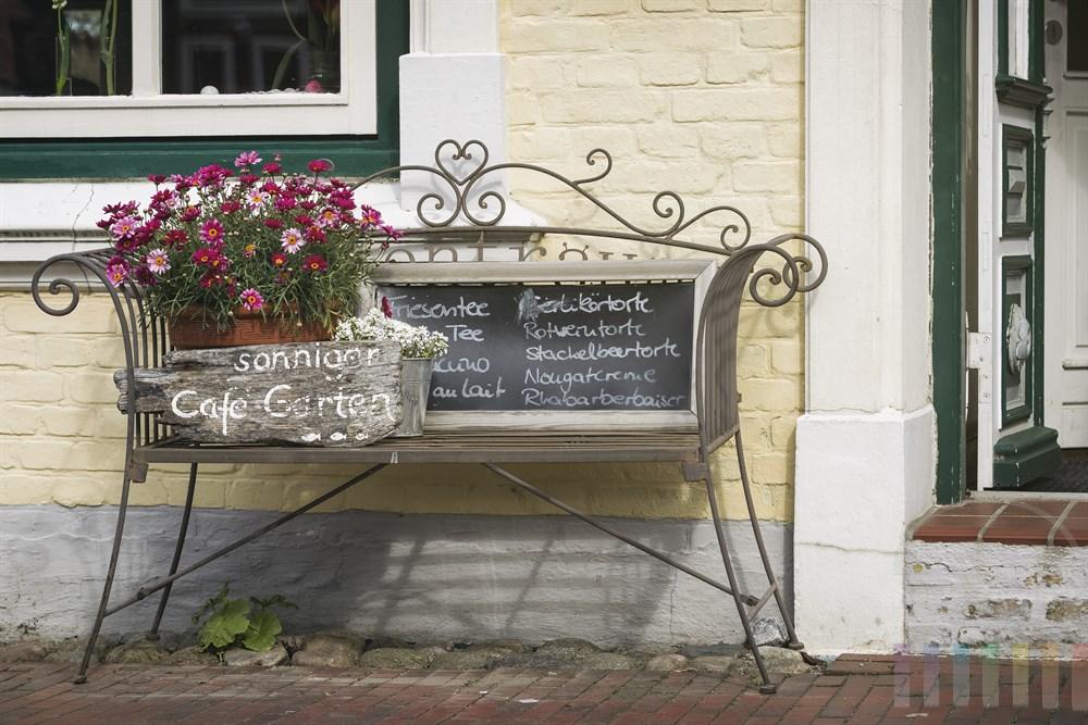 Dekorative Bank mit Blumenkübel vor dem Eingang zu einem Café weist auf auf einen sonnigen Garten sowie leckere Torte hin