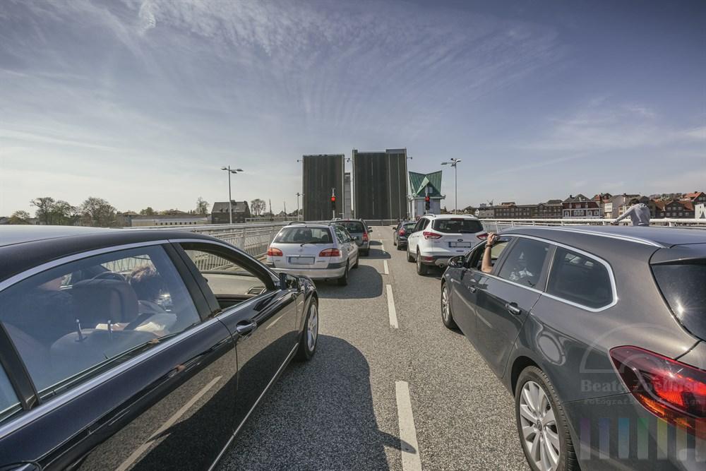 Autos stehen wartend vor hochgeklappter Brücke über die Schlei in Kappeln, sonnig