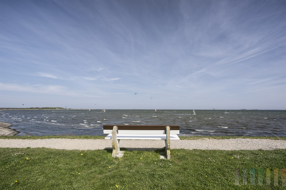 Parkbank bietet einen tollen Blick auf die Schlei zwischen Maasholm und Schleimünde. Wind- und Kitesurfer nutzen den kräftigen, auflandigen Wind für ihren Sport, sonnig.