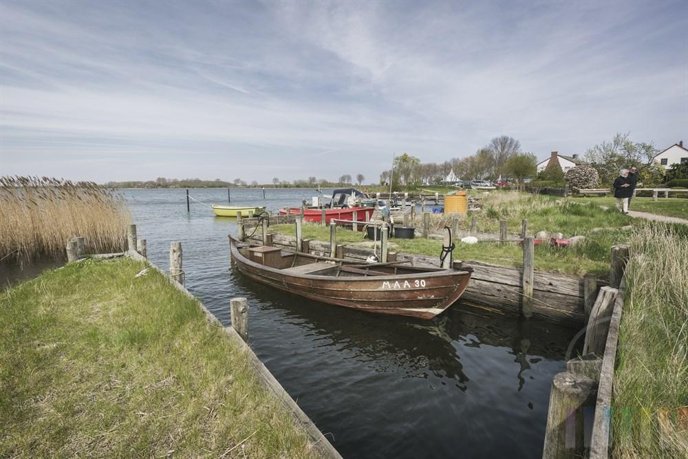 """Altes Fischerboot liegt in einer für die Gegend so typischen """"Kahnstellen"""" am Schleiufer in Maasholm. Diese mit Holz eingefassten Bootsliegeplätze stehen unter Denkmalschutz. Knapp 50 Stück gibt es noch in dem malerischen Fischerdorf."""