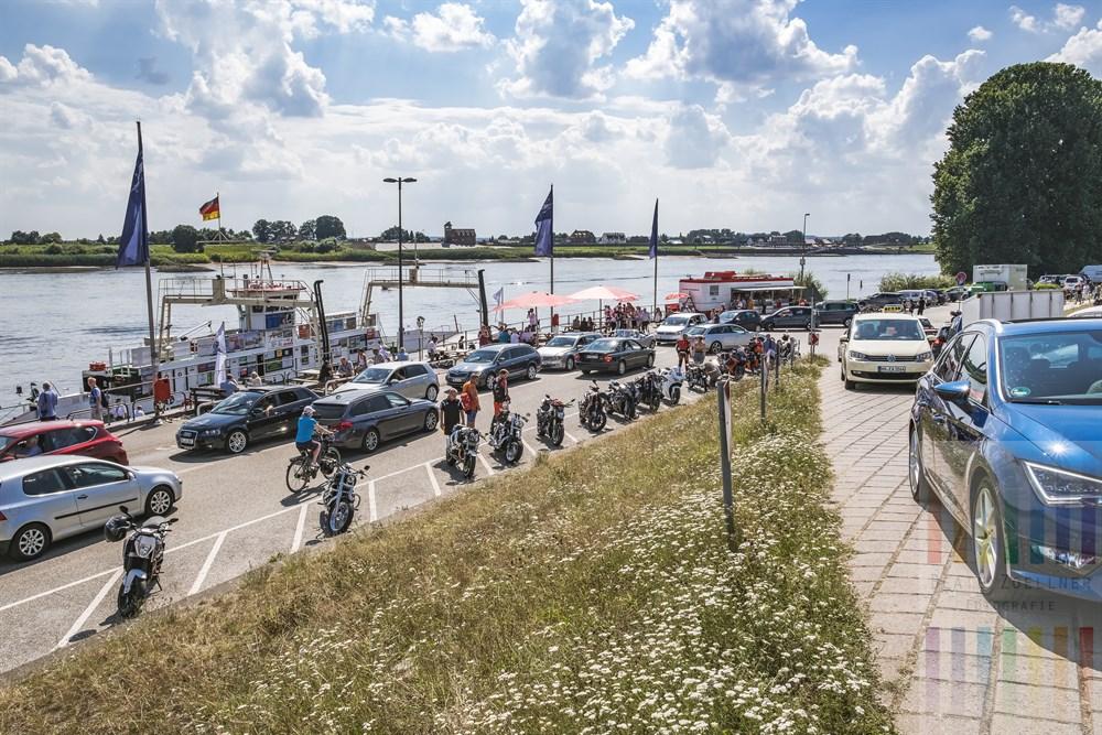 Hochsommertag an der Elbfähre in Hamburg-Zollenspieker. Zahlreiche Ausflügler mit Motorrad, Fahrrad oder Auto pendeln über den Fluss nach Hoopte auf niedersächsischem Boden