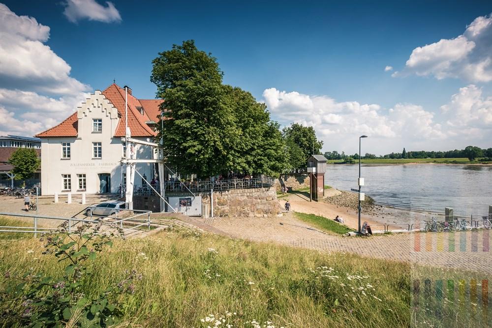 Blick vom Elbdeich auf das Zollenspieker Fährhaus an einem heißen Sommertag. Das historische Gebäude steht am südlichsten Punkt Hamburgs direkt am Ufer der Elbe. Es steht unter Denkmalschutz und ist ein beliebtes Ausflugsziel.