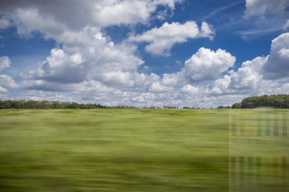 Sommerliche Fahrt durch scheinbar vorbei fliegende norddeutsche Landschaft in der Nähe von Alveslohe (Kreis Segeberg)