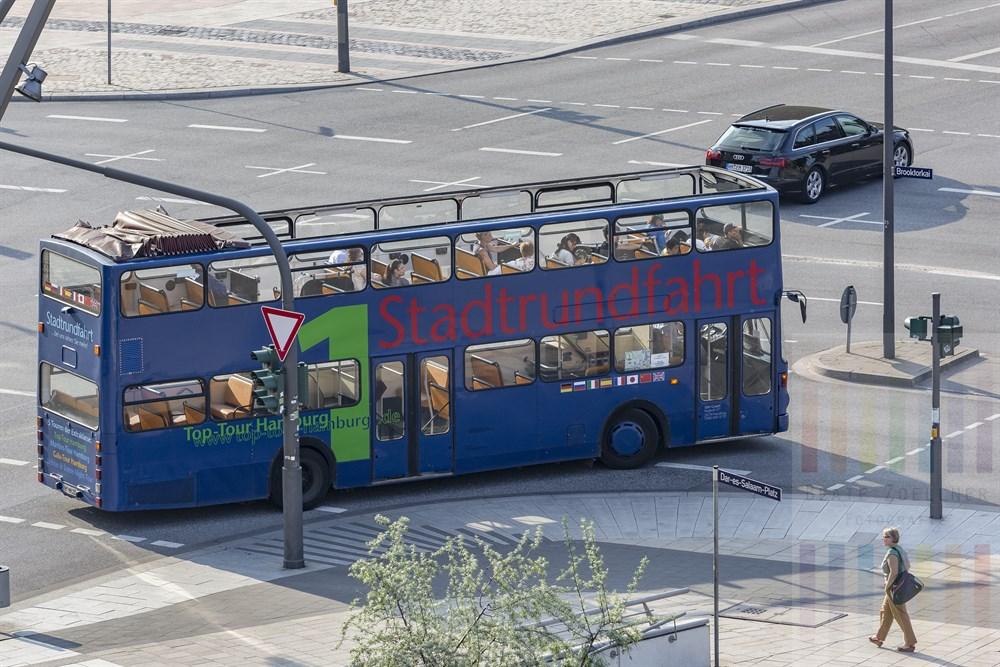 Cabrio-Doppeldecker-Bus biegt mit Touristen von der Osakaallee in der Hamburger Hafencity in die Straße Brooktorkai ab