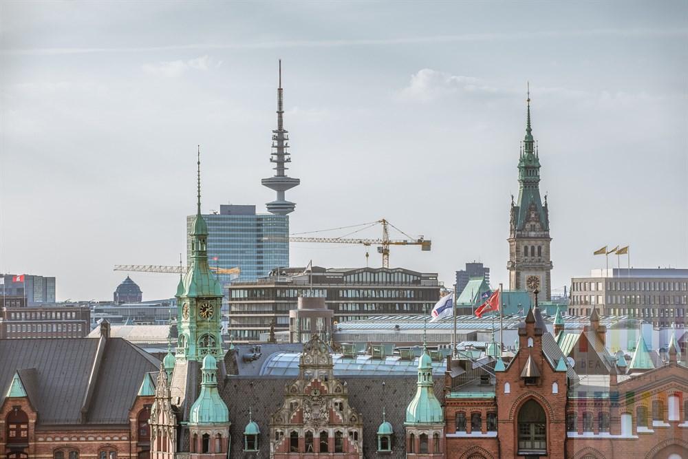 Blick vom Internationalen Maritimen Museum über die historische Speicherstadt und moderne Geschäftshäuser auf Rathaus und Fernsehturm der Hansestadt Hamburg, sonnig