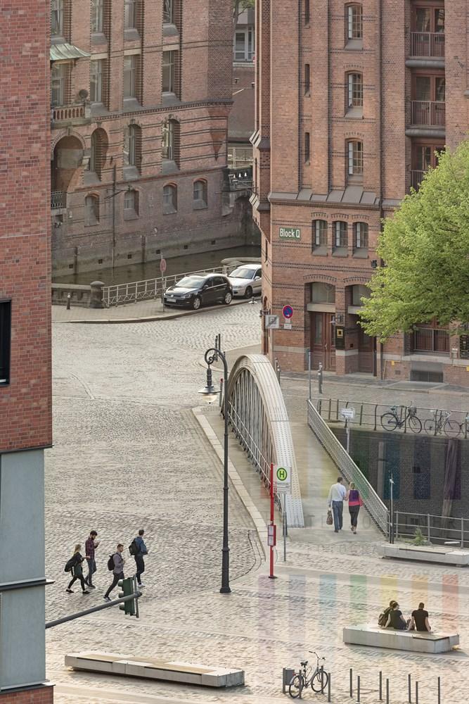 Blick vom Internationalen Maritimen Museum auf den St.Annenplatz in der Hamburger Speicherstadt. Menschen sitzen nach Feierabend auf dem St. Annenplatz und geniessen die Frühlingssonne