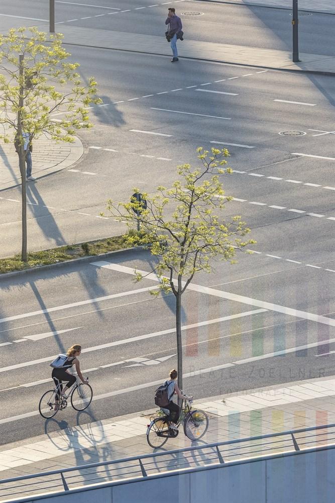 Straßenkreuzung Osakaallee/Am Sandtorkai in der Hamburger Hafencity im Licht der tiefstehenden Abendsonne. Zwei Radahrerinnen und zwei Fußgänger sind unterwegs. Blick vom Internationalen Maritimen Museum Hamburg