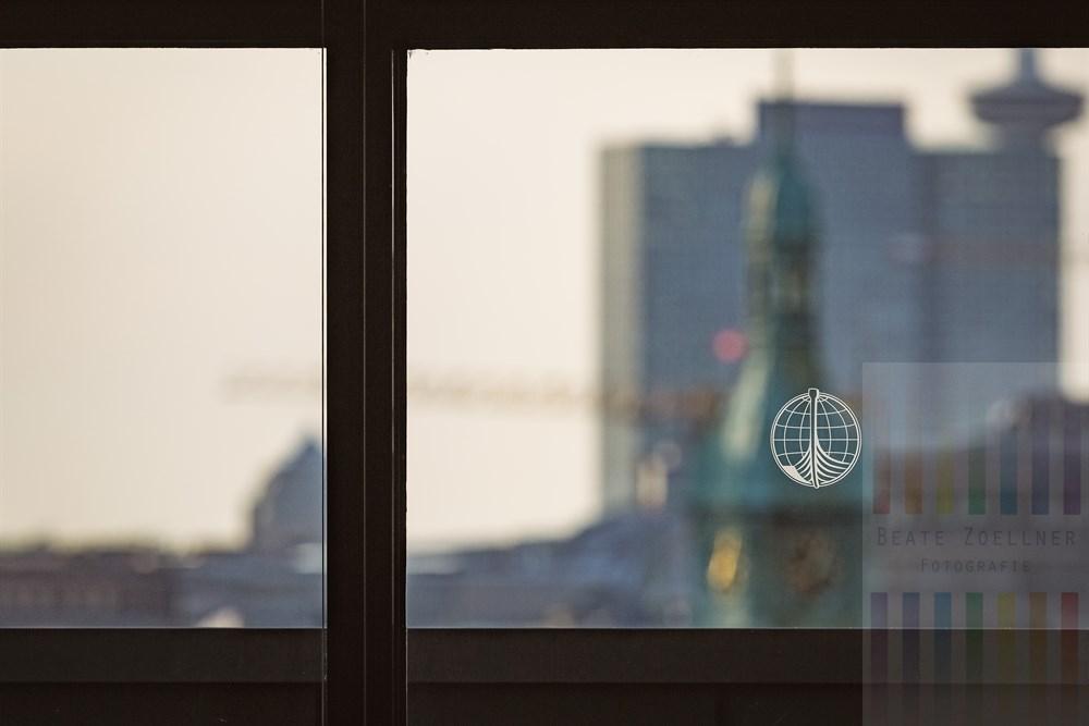Blick durch Fenster des Internationalen Maritimen Museums in Hamburg auf die Türme der Stadt.Auf der Glasscheibe das Logo des Museums