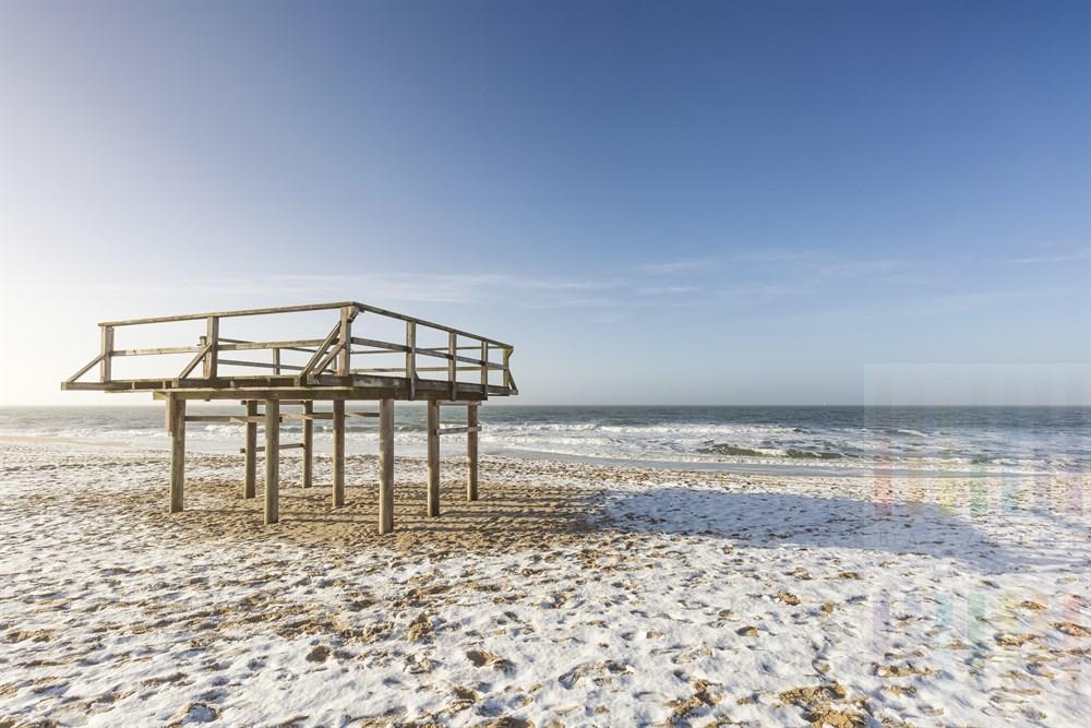Wenige Zentimeter Schnee liegen bei strahlendem Sonnenschein und blauem Himmel am Strand von Westerland/Sylt. Auf dem Holzpodest steht während der Bade-Saison die Hütte der Rettungschwimmer.