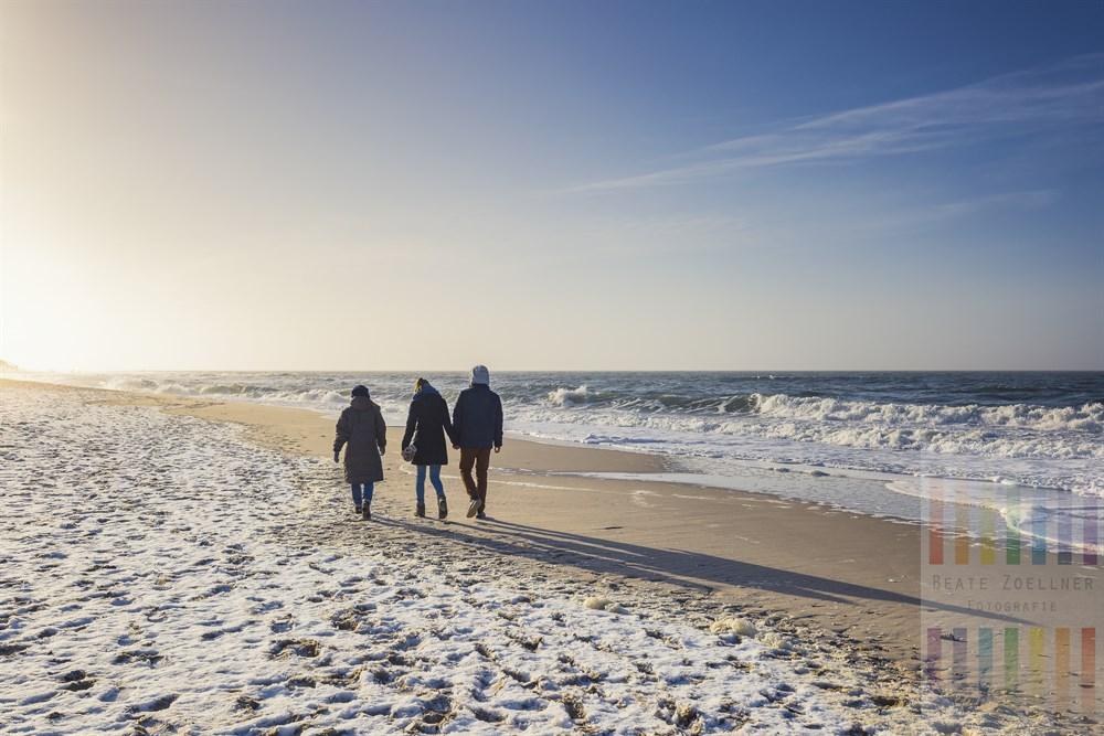 Drei Urlauber spazieren bei strahlendem Sonnenschein am leicht verschneiten Strand von Westerland/Sylt der Sonne entgegen