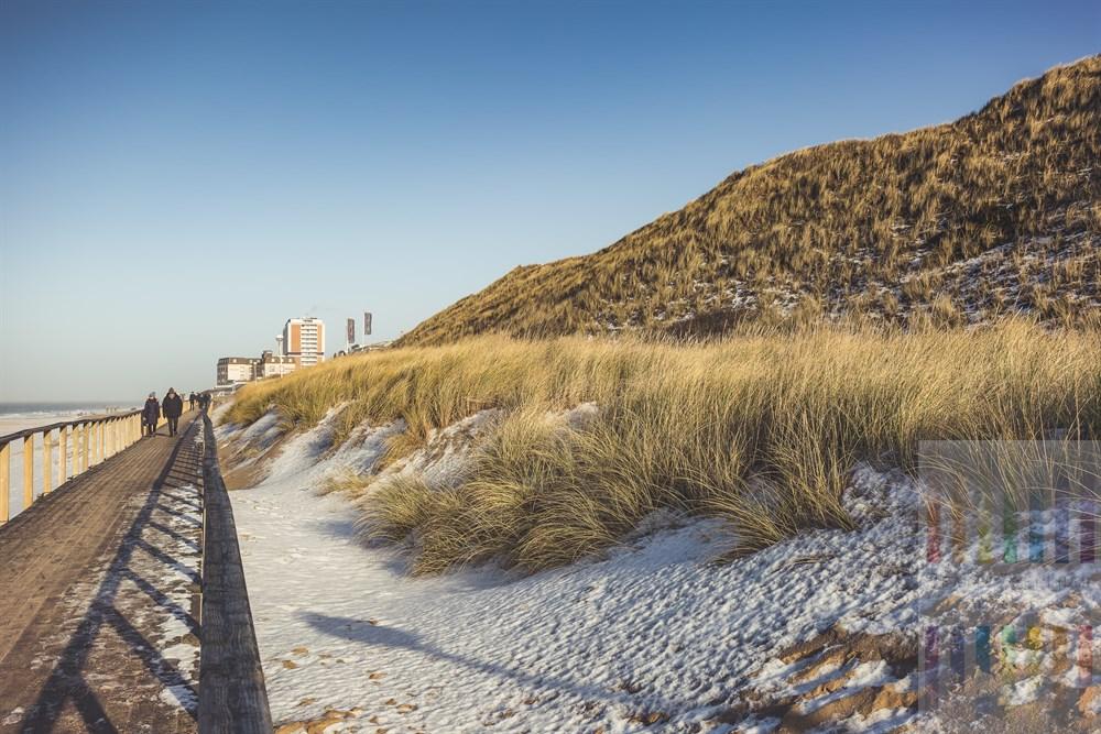 Sonniger Januartag am Strand von Westerland/Sylt. Eine dünne Schneeschicht liegt am Fuße der Dünen