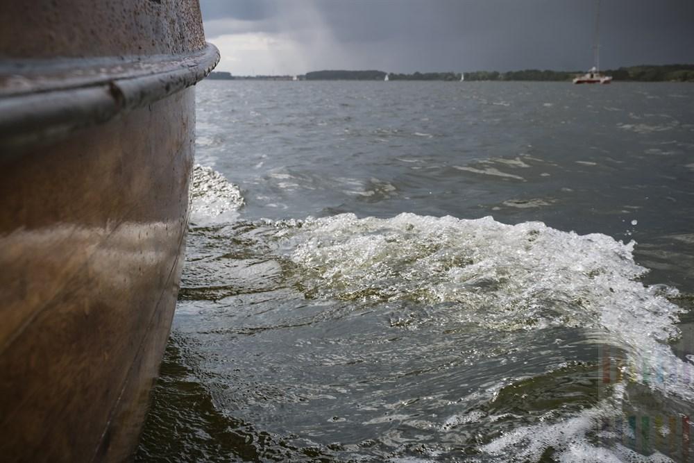 Hölzerne Bordwand eines alten Kutters während eines Segeltörns auf der Schlei. Nur wenige Sonnenstrahlen durchdringen die grauen Regenwolken am Himmel