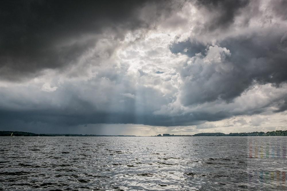 Dunkle, bedrohliche Wolken brauen sich über der Schlei zusammen, lassen aber einen Durchlass für ein paar Sonnenstrahlen