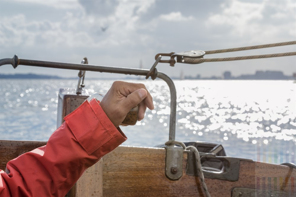 Männerhand an der Pinne eines alten Holz-Segelbootes. Im Hintergrund die Schlei