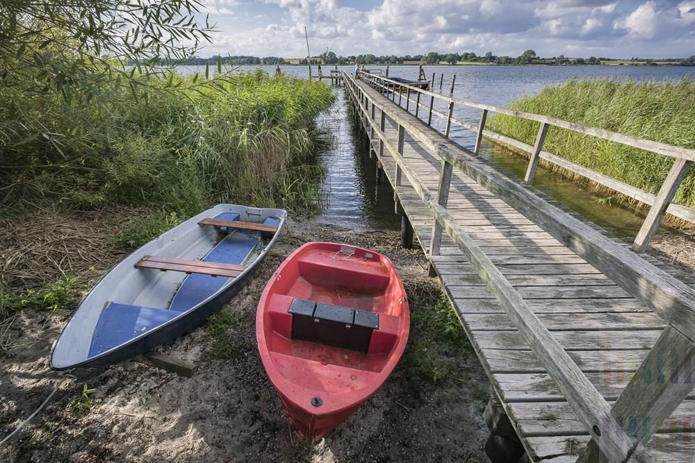 Ein rotes und ein blaues Boot liegen am Ufer neben dem Bootssteg in Sieseby an der Schlei