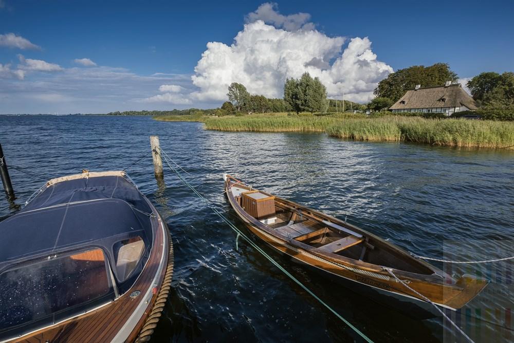 Holzboote liegen am Steg an der Schlei bei Sieseby, im Hintergrund ein historisches, reetgedecktes Fachwerkhaus