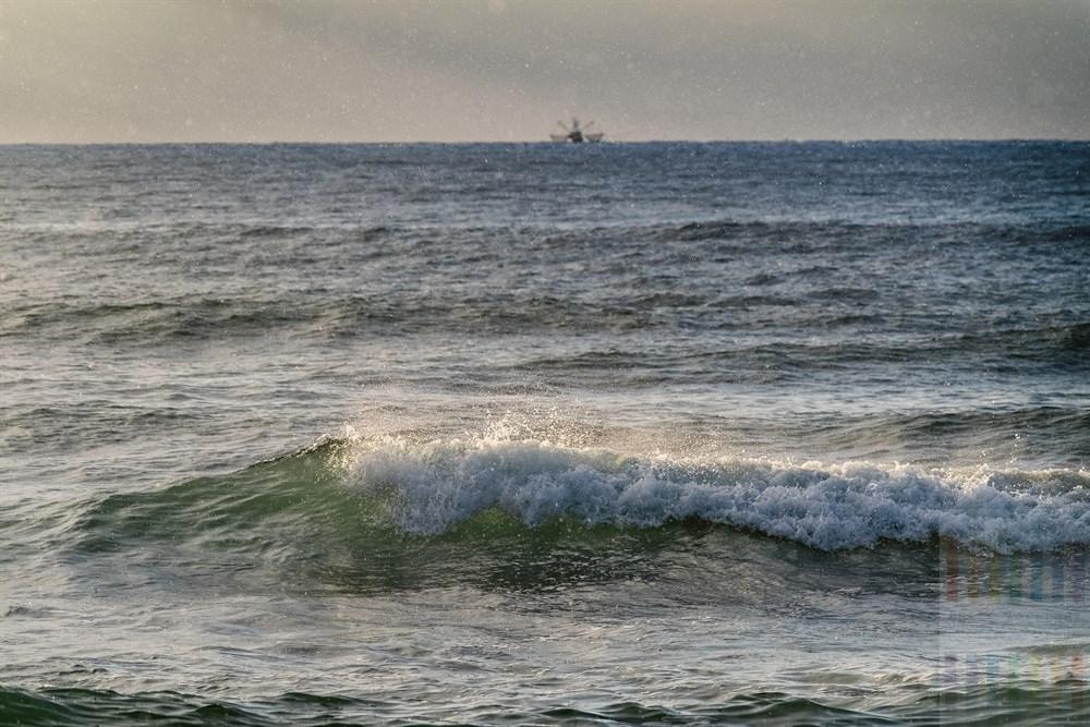 Sonnenstrahlen lassen Regentropfen und Nordseegischt im Licht glitzern, am Horizont die Silhouette eines Krabbenkutters auf Fangtour