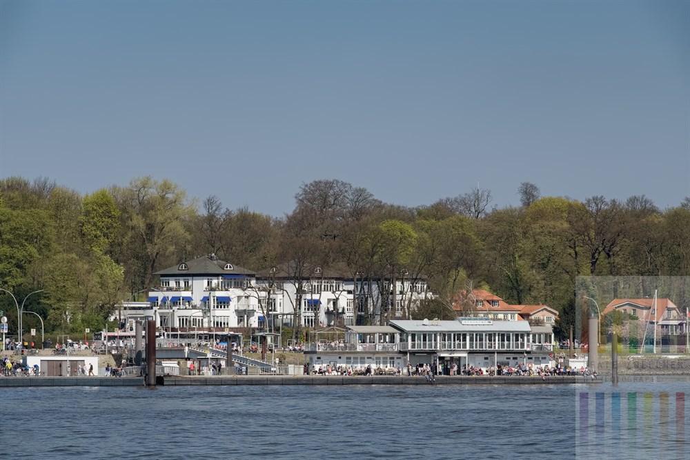 Blick von Hamburg-Finkenwerder über die Elbe auf den Anleger mit dem Café Engel in Teufelsbrück an der Elbchaussee. Viele Menschen genießen den sonnigen Frühlings-Sonntag