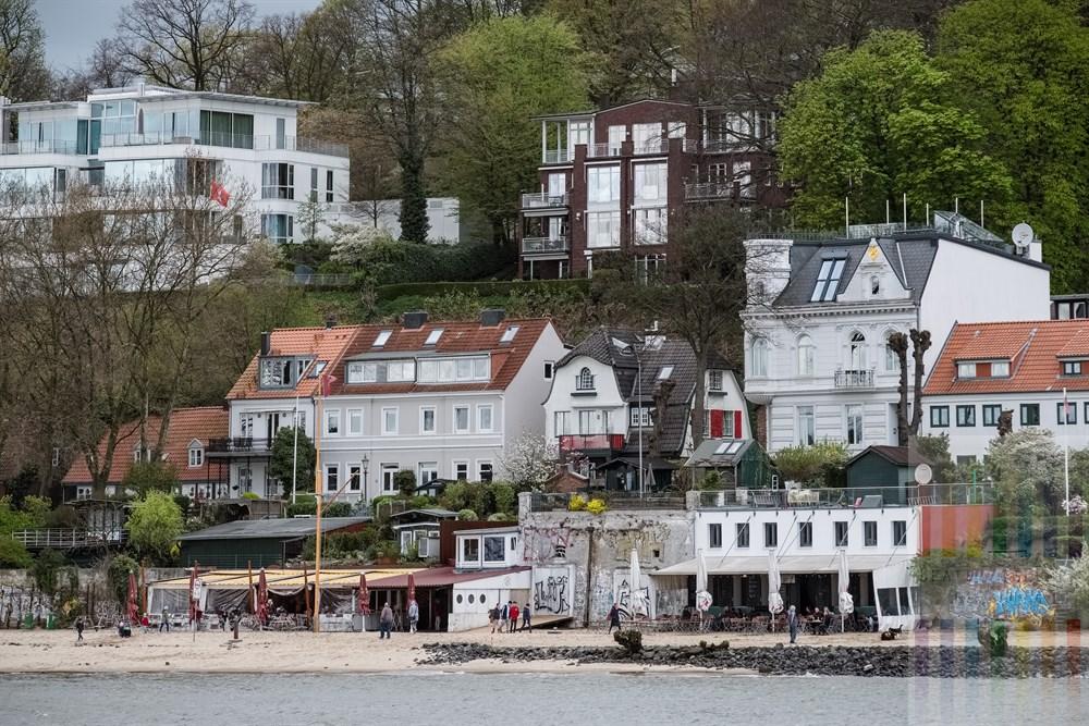"""Blick von der Elbe auf die legendäre Kult-Gastronomie """"Strandperle"""" (links) und """"Strand-Kiosk"""" am Flussufer. Darüber die schmucken teilweise historischen Wohnhäuser und noch eine Etage höher stehen riesige Villen in moderner Architektur"""