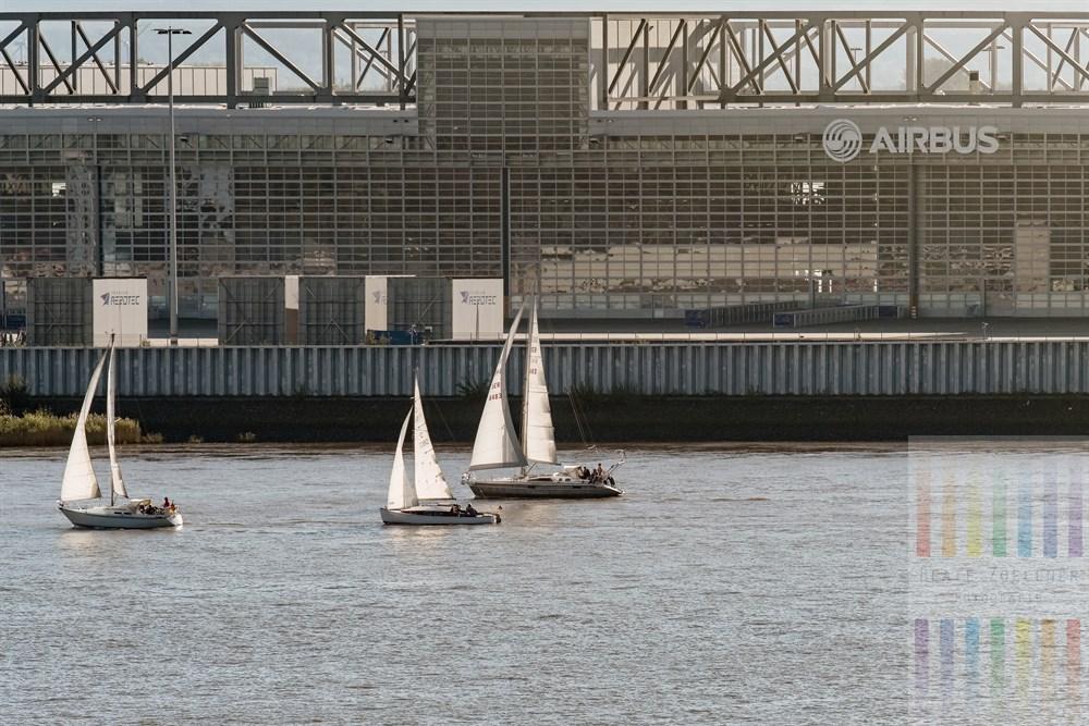 Blick vom Hirschpark in Hamburg-Nienstedten über die Elbe auf die riesigen Werkshallen von Airbus in Hamburg-Finkenwerder. Drei Segelboote passieren das Gebäude Richtung Hafen