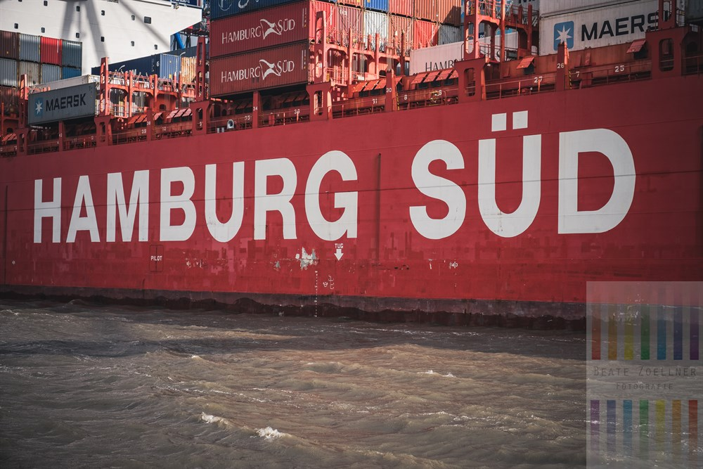 """Rote Bordwand des Containerschiffes """"Monte Alegre"""" der Reederei """"Hamburg-Süd"""". Der Frachter liegt am Burchard-Kai im Hamburger Hafen - Blick von Bord der Elbfähre """"Kleine Freiheit"""""""