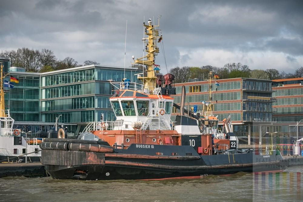 """Blick von Bord der Elbfähre """"Kleine Freiheit"""" über die Elbe auf dien Hamburger Schlepper """"Bugsier 10"""" an der Station in Hamburg-Neumühlen, dahinter moderne Bürogebäude"""