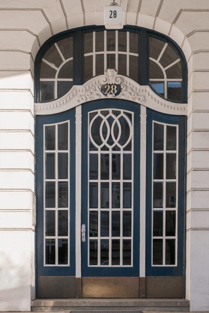 Aufwändig gestaltete Haustür eines fünfgeschossigen Wohnhauses von 1908 in Hamburg Eimsbüttel. Das Gebäude ist denkmalgeschützt
