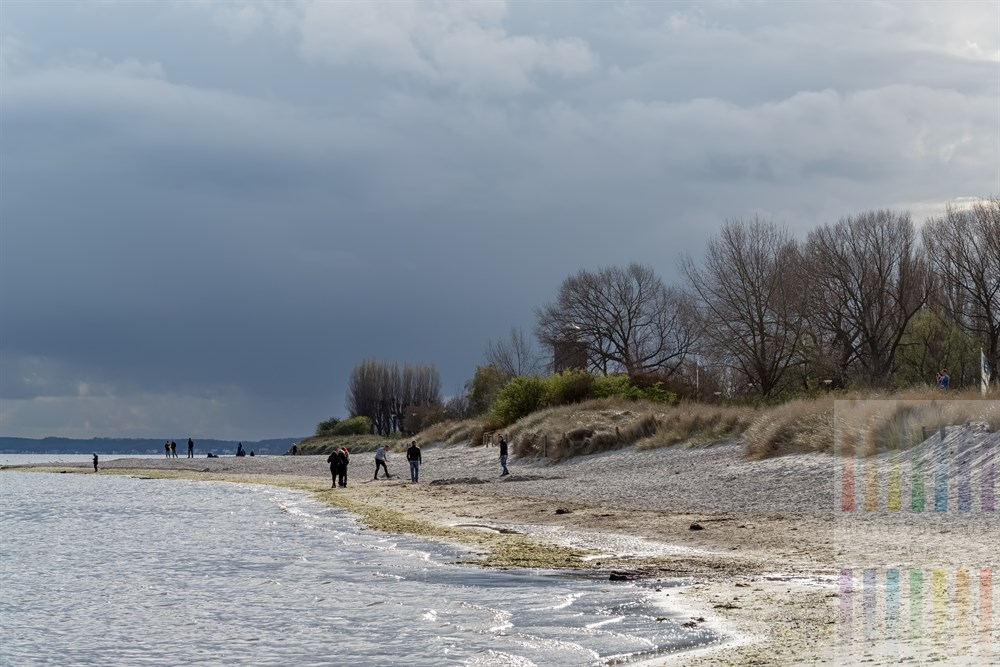 Menschen am Strand von Pelzerhaken, über ihnen bleigrauer Wolkenhimmel, während gleichzeitig die Sonne scheint