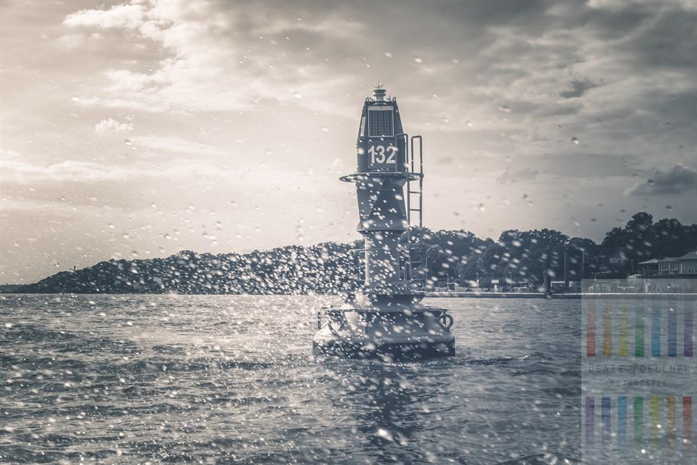 Fahrwassertonne auf der Elbe vor dem Schiffsanleger in Hamburg-Teufelsbrück. Im Vordergrund Wasserspritzer, die vom Bootsmotor aufgewirbelt wurden. Monochrome Version