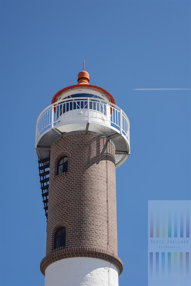Fassade und Spitze des Leuchtturms von Timmendorf auf der Insel Poel vor wolkenlos blauem Sommerhinnel Ein Flugzeug durchzieht den Himmel mit seinem Kondensstreifen