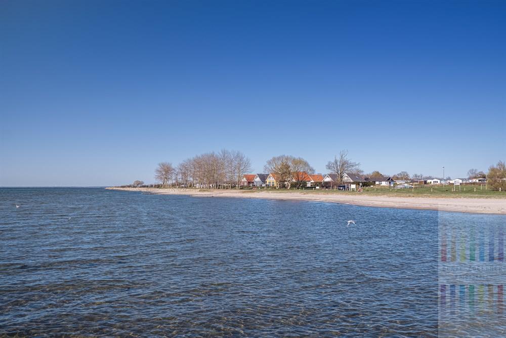 Ferienhäuser, Campingplatz und Strand von Wackerballig an der Geltinger Bucht. Das Wasser der Ostsee ist glasklar, der blaue Himmel wolkenlos