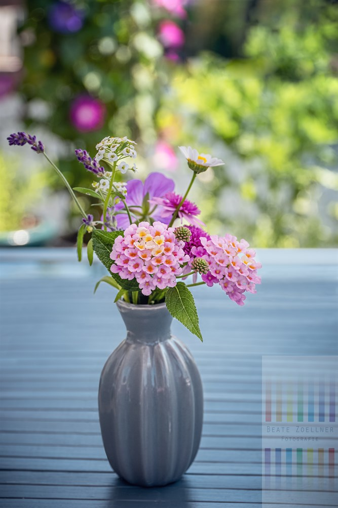 Kleiner Sommerblumenstrauß steht auf einem Gartentisch im Freien