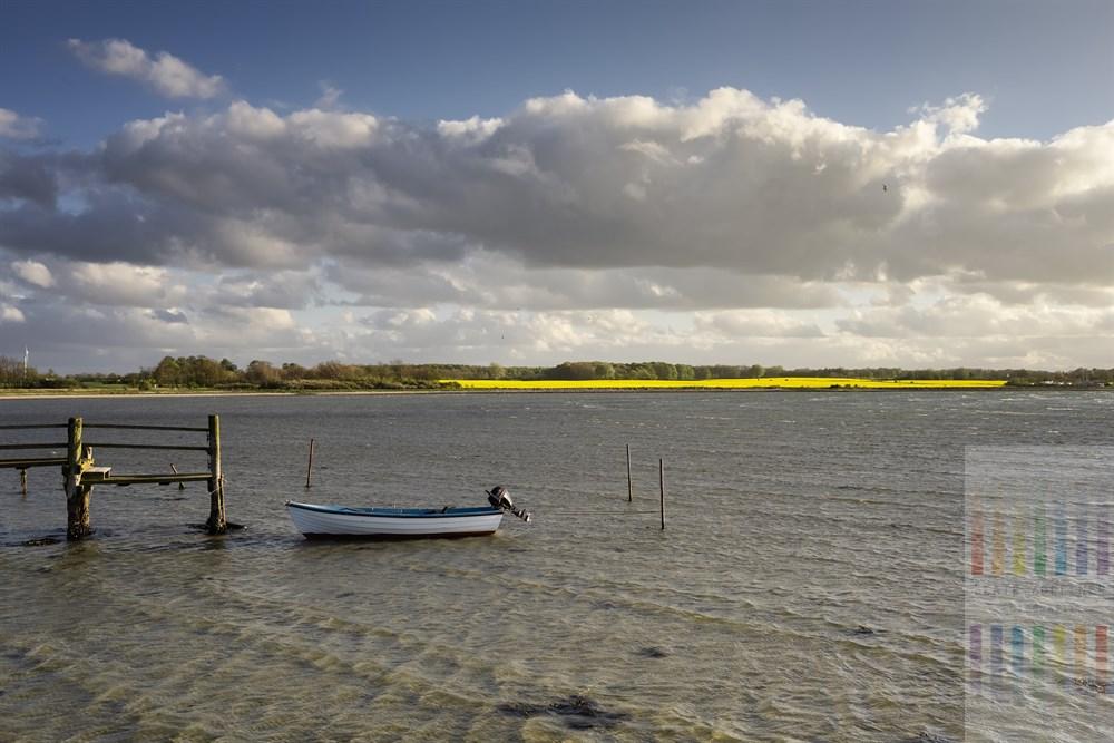 Windiger Frühlingsabend in Wackerballig in der Geltinger Bucht: Ein kleines Boot dümpelt an einem hölzernen Steg im Licht der Frühlingssonne. Im Hintergrund leuchtet gelb ein Rapsfeld