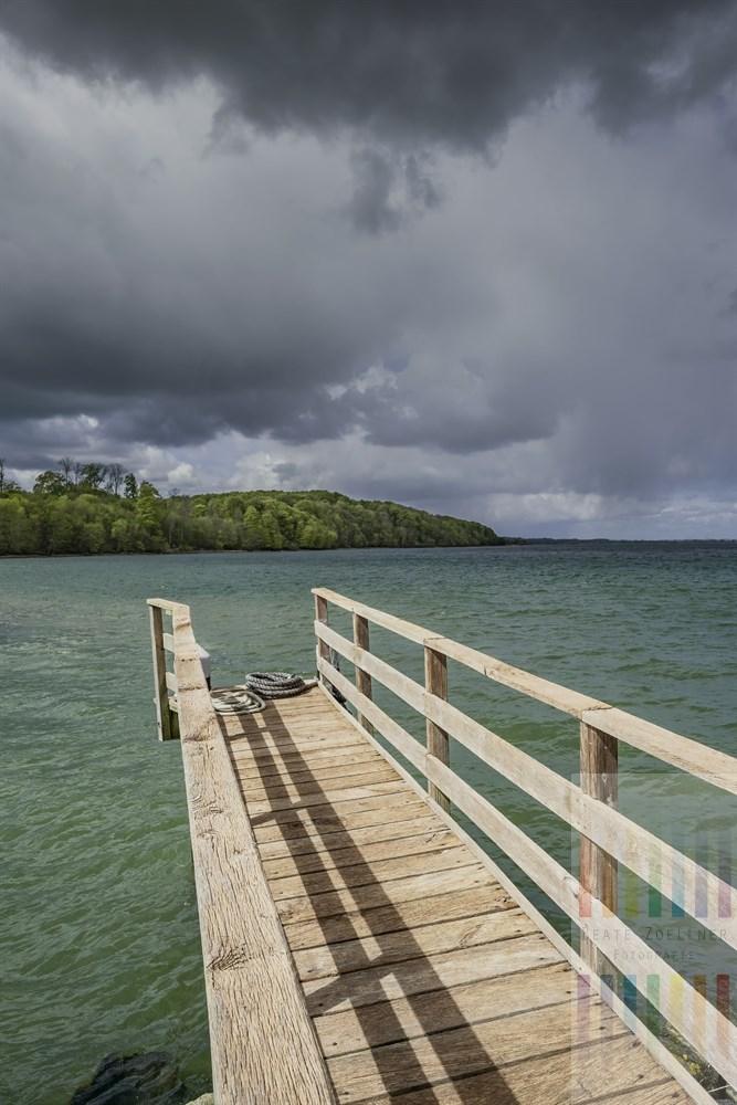 Bedrohliche Gewitterwolken über der Flensburger Förde. Die Frühlingssonne bescheint im Vordergrund noch einen hölzernen Steg am Hafen von Langballigau