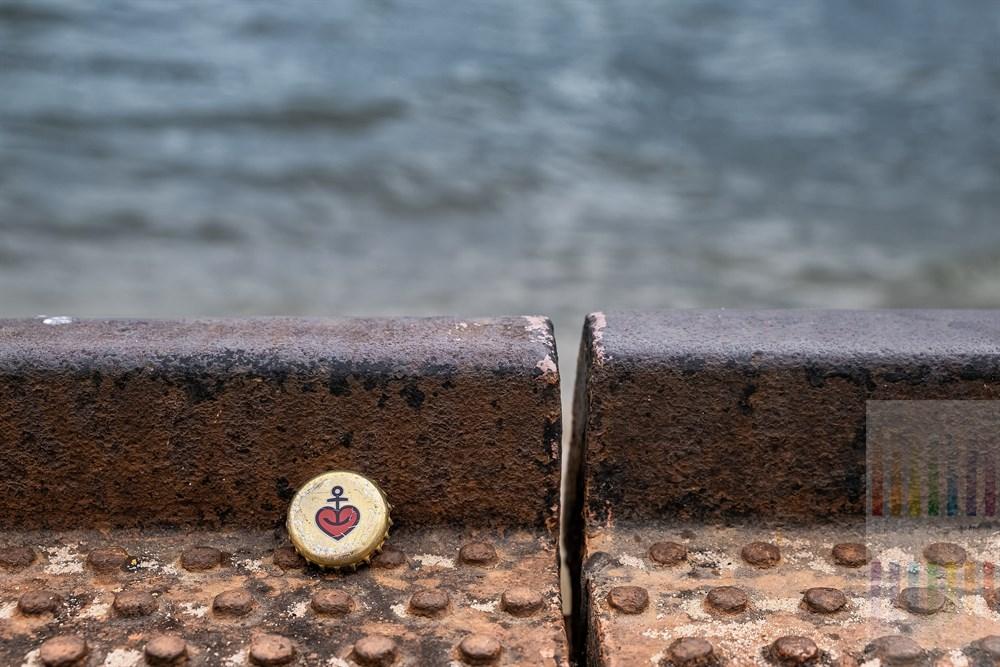 zerkratzter Kronkorken der Hamburger Biermarke Astra liegt auf dem Boden eines stählernen Schiffsanlegers an der Elbe