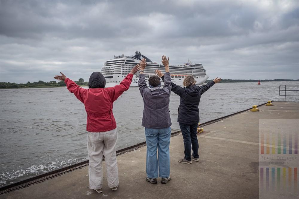 """Drei ältere Frauen stehen auf dem Schiffsanleger Hamburg-Wittenbergen und winken dem auslaufenden Kreuzfahrtschiff """"MSC Orchestra"""" zum Abschied. Das Wetter ist alles andere als sommerlich"""