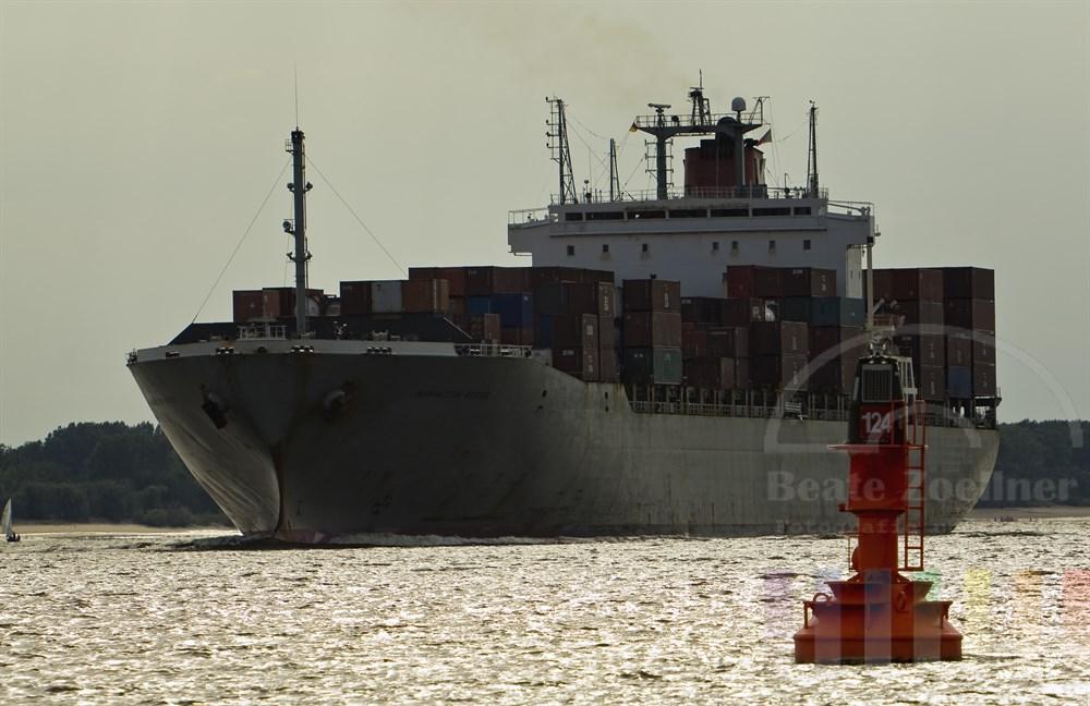 voll beladenes Containerschiff MANHATTAN BRIDGE läuft im Abendlicht den Hamburger Hafen an. Im Vordergrund ein Seefahrtszeichen, das die Fahrrinne markiert. Vor dem Bug des Schiffes treibt ein Segelboot auf der Elbe