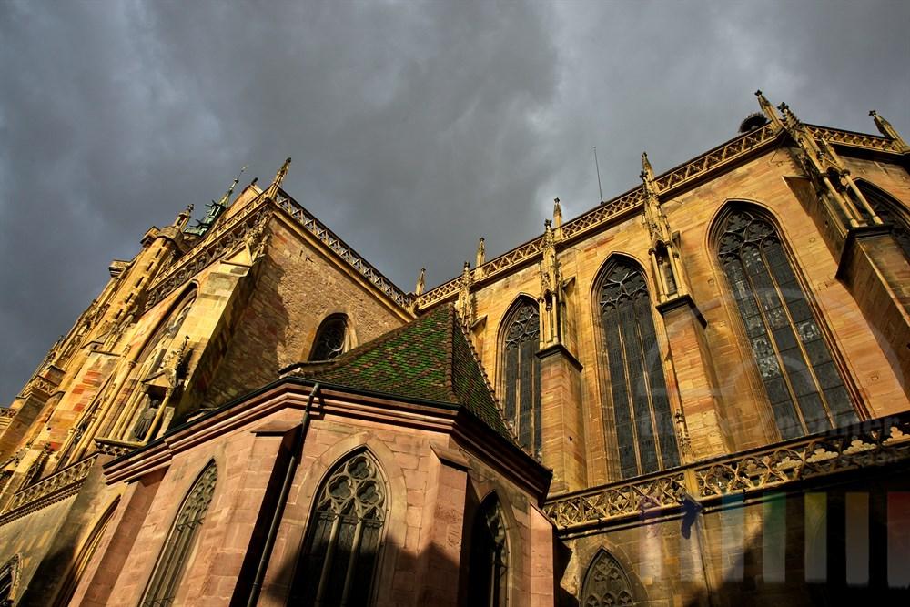 """Die Stiftskirche St. Martin in Colmar, von den Elsässern meist """"Kathedrale"""" genannt, wird von der Herbstsonne angestrahlt. Darüber grauer Wolkenhimmel"""