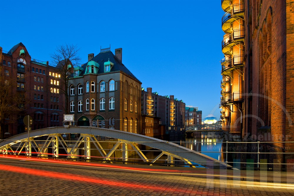 """lanfzeitbelichtung zur Blauen Stunde: Historische Brücke in der Hamburger Speicherstadt, im Hintergrund bewegt sich der """"High Flyer"""" (ein Fesselballon) im Wind hin und her"""