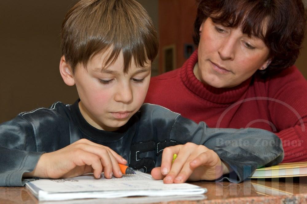 Mutter hilft ihrem Sohn im Grundschulalter (3. Klasse) bei den Hausaufgaben