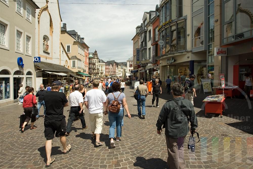 Touristen in sommerlicher Kleidung bummeln durch die Altstadt von Trier auf den Hauptmarkt zu