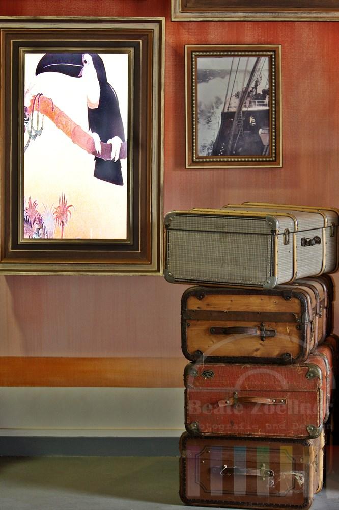 zeitgenössische Reisekoffer vor Bilderrahmen mit modernen Video-Installationen dekorieren den Eingangsbereich zur Ausstellung