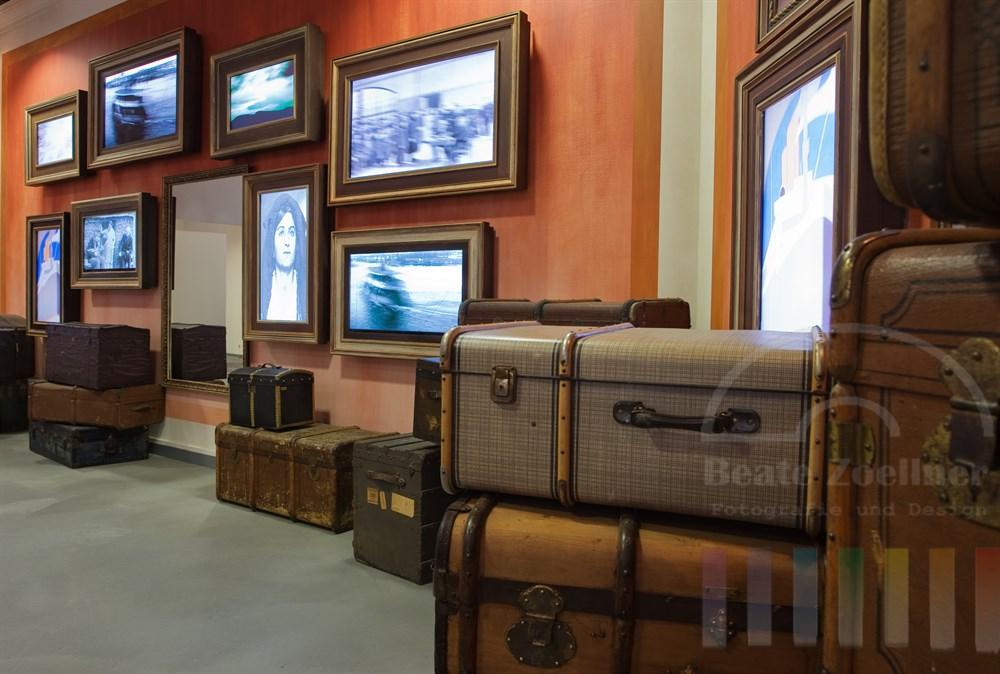 Ausstellung in der BallinStadt zum Thema Auswanderung: historische Überseekoffer und Seekisten in einem Raum mit Videoinstallationen in Bilderrahmen